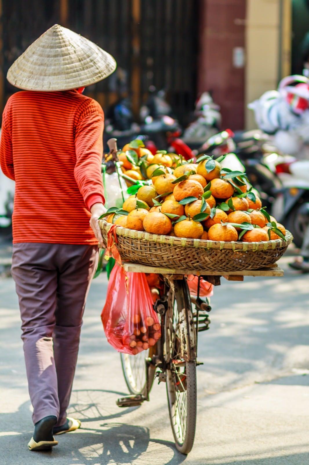 Marchande clémentine asiatique à vélo.
